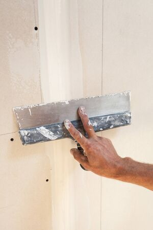 plasterboard: Man hand with trowel plastering a plasterboard