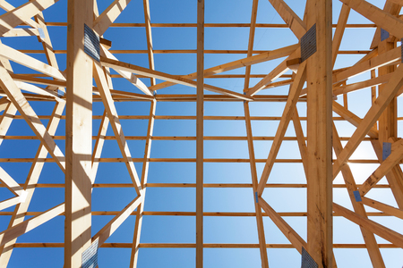 residential home: New residential wooden construction home framing against a blue sky