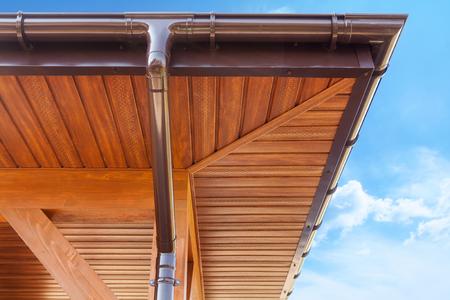 Brown copper gutter under a cloudy blue sky
