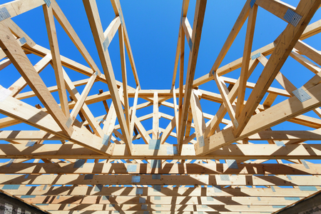 architectural exterior: New residential wooden construction home framing against a blue sky