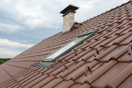 light slate gray: New roof with skylight, natural red tile and chimney Stock Photo