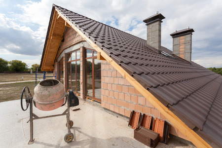 View on the tiled roof with chimneys from second floor of a new house Stock Photo