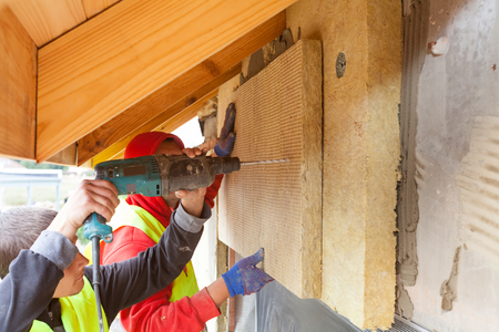 glasswool: Workers installing mineral rockwool panel on the wall. House insulation for better energy efficiency
