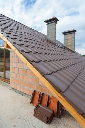 second floor: View on the tiled roof with chimneys from second floor of a new house Stock Photo