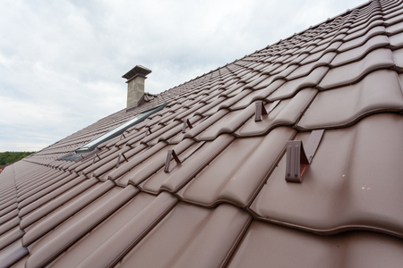 light slate gray: New roof with skylight, natural red tile and chimney with snow stopers Stock Photo