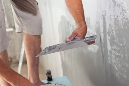 home repairs: Closeup of repairman hand plastering a wall with putty knife or spatula Stock Photo