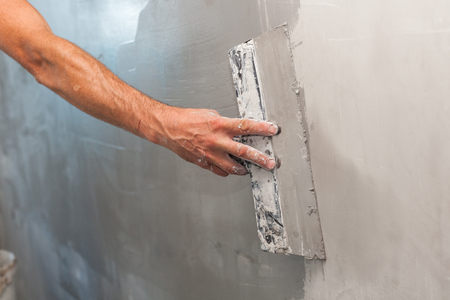 patching: Man hand with trowel plastering a wall Stock Photo