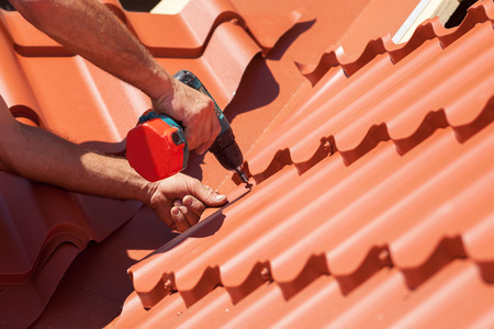 Worker on a roof with electric drill installing red metal tile on wooden house Archivio Fotografico