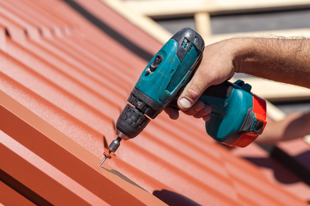 Worker on a roof with electric drill installing red metal tile on wooden house Banque d'images