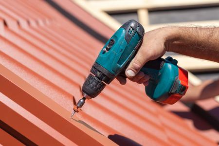 Werknemer op dak met elektrische boorinstallatie van rode metalen tegel op houten huis