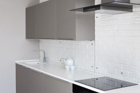down lights: White new modern kitchen with counter top and exhaust hood