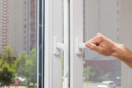 man hand ouvre une fenêtre en plastique pvc