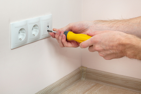 energy work: The hands of an electrician installing a wall power socket