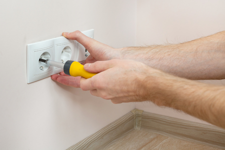 The hands of an electrician installing a wall power socket with screwdriver Stock Photo