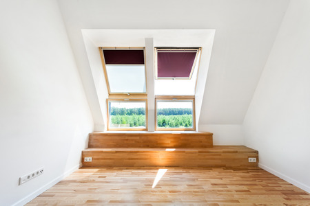 Empty Room of New Home with Wood Floors, White Walls and Bright Skylights