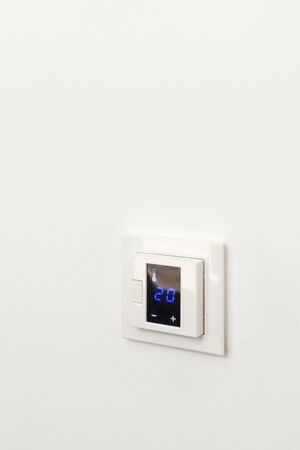 Digital climate control on white wall