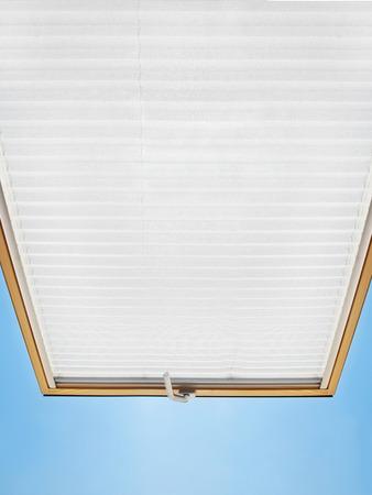 Een modern geopend mansardvenster in een zolderkamer tegen de blauwe hemel Stockfoto
