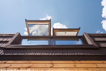 mansard: Open skylights (mansard windows) in wooden house with tile against blue sky