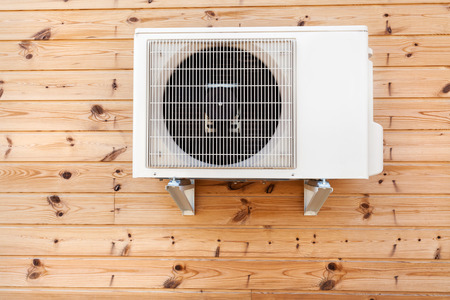Exterior airconditioning unit on a wooden wall