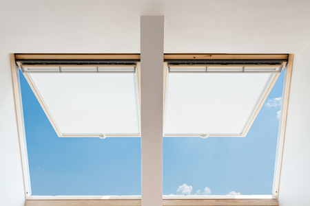 A modern open skylights (mansard windows) in an attic room against blue sky