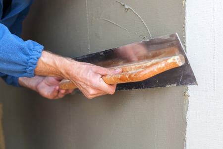 skimming: Construction worker with long trowel plastering a wall Stock Photo