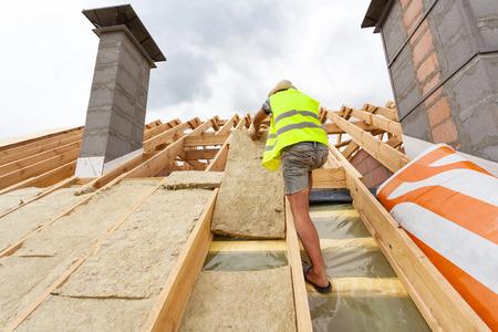 De bouwersarbeider die van Roofer het materiaal van de dakisolatie (rockwool) installeren op nieuw huis in aanbouw
