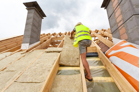 Roofer builder worker installing roof insulation material (rockwool) on new house under construction Standard-Bild