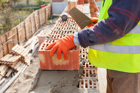 Construction mason worker bricklayer installing red brick with trowel putty knife outdoors Reklamní fotografie - 82833790