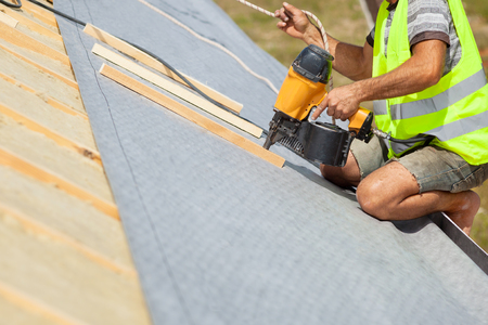 roofing membrane: Roofer builder worker use automatic nailgun to attach roofing membrane Stock Photo