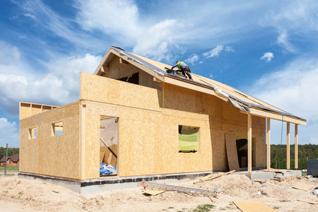 Construction or repair of  house with insulation, eaves, windows, garage,chimney, roofing, fixing facade and plastering Stock Photo