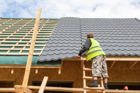 Roofer worker installing a metal tile on a new wooden house