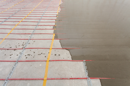 Electric floor heating system installation in new house. Closeup of concrete and red electrical wires