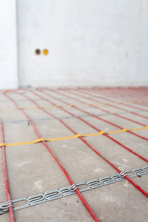 Electric floor heating system installation in new house. Closeup of  red electrical wires