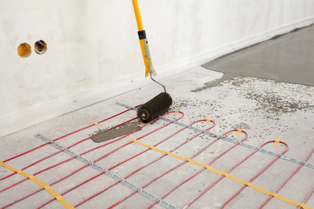 Electric floor heating system installation in new house. Closeup of concrete, roller and red electrical wires Reklamní fotografie