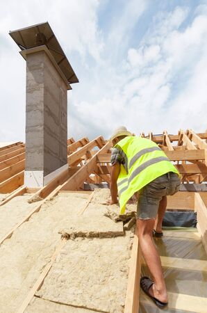 roofing membrane: Roofer builder worker installing roof insulation material on new house under construction Stock Photo