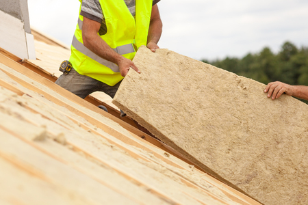 Roofer builder worker installing roof insulation material on new house under construction Stock Photo