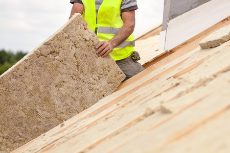 plasterer: Roofer builder worker installing roof insulation material on new house under construction Stock Photo