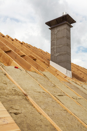 rockwool: Roof insulation (rockwool). New house under construction with chimney