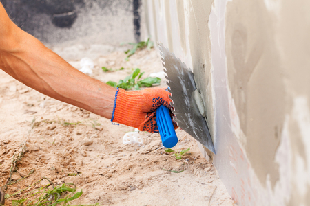 Construction worker plastering a wall and house foundation with trowel