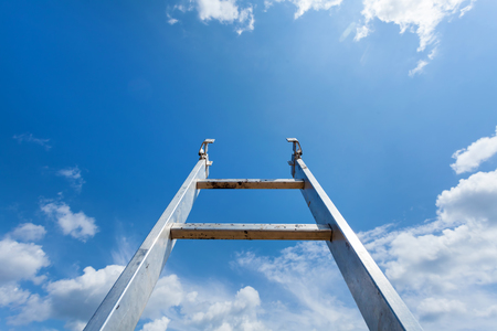 Ladder reaching into a blue sky and clouds