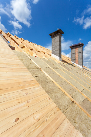 Roof insulation. New wooden house under construction with chimneys against blue sky