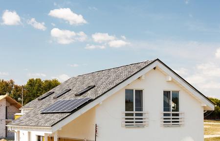 Solar water panel verwarming aan nieuw huis dak met dakramen tegen de blauwe hemel Stockfoto
