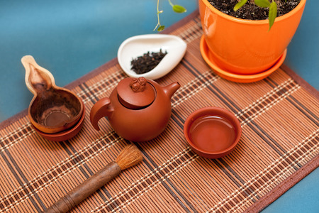 tea hot drink: Teapot,tea cup and tea leaves on a bamboo mat Stock Photo