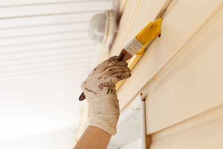 Worker with gloves colors the metal gas pipe of yellow paint with a brush with a wooden handle. Stock Photo