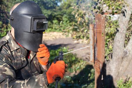 Man in welding mask welds metal corner. Welding metal. Steel welder. Welder working with electrode. Stock Photo