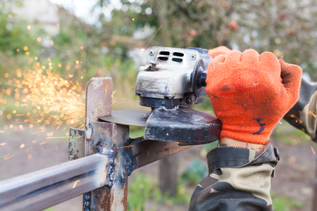 cut off saw: Closeup of a man using a grinder with cutoff blade to cut a section of pipe