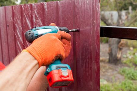 Metallzauninstallation. Arbeiter in Handschuhen mit einem Bohrer baut neuen Metallzaun.