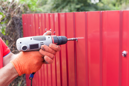 Metal fence installation. Work man in gloves with a drill builds new metal fence.