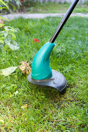 Worker mows a lawn mower. Green lawn mowercloseup. Stock Photo