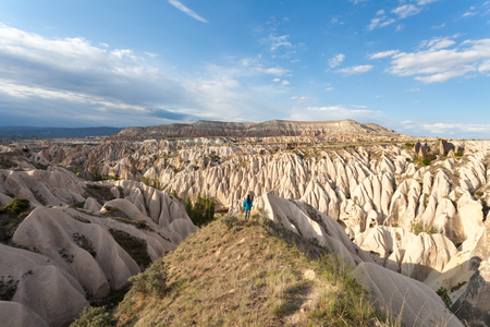 The girl looks at the wonderful landscape of Cappadocia in Turkey, near Goreme. Pink and Red Valley. Stock Photo